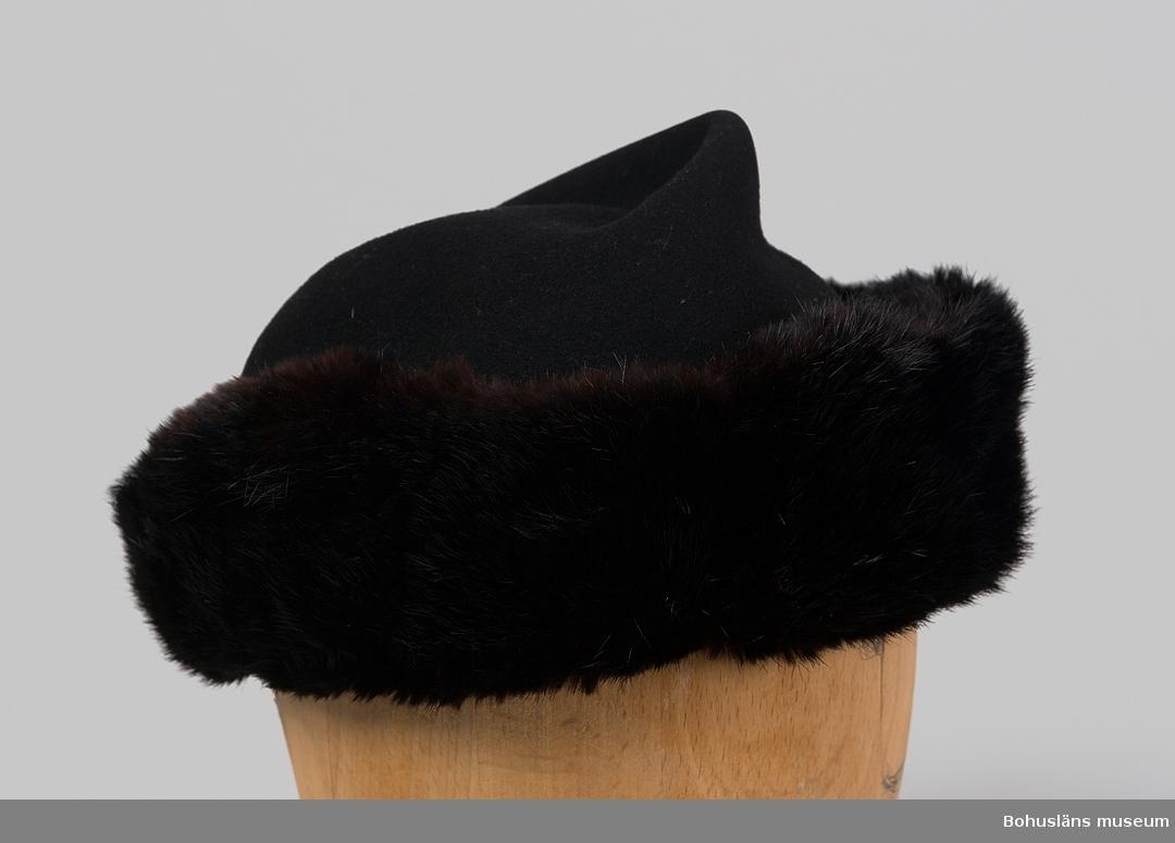 """Svart med brun-svart pälsbräm för dam. Rund, mjuk kulle vilken sluttar bakåt. Pälsbrämets ändar är placerade baktill. Ändarna avrundas bakåt och mitt bak vid hattkanten är det ingen päls. Fodrad med svart tyg med randig struktur troligen gjort av regnatfiber. I fodret är en tygetikett med texten: """"GAM FABRIKAT"""" fastsydd. Hatten är använd tillsammans med muff UM026416  Historik om brukaren; se UM26414."""