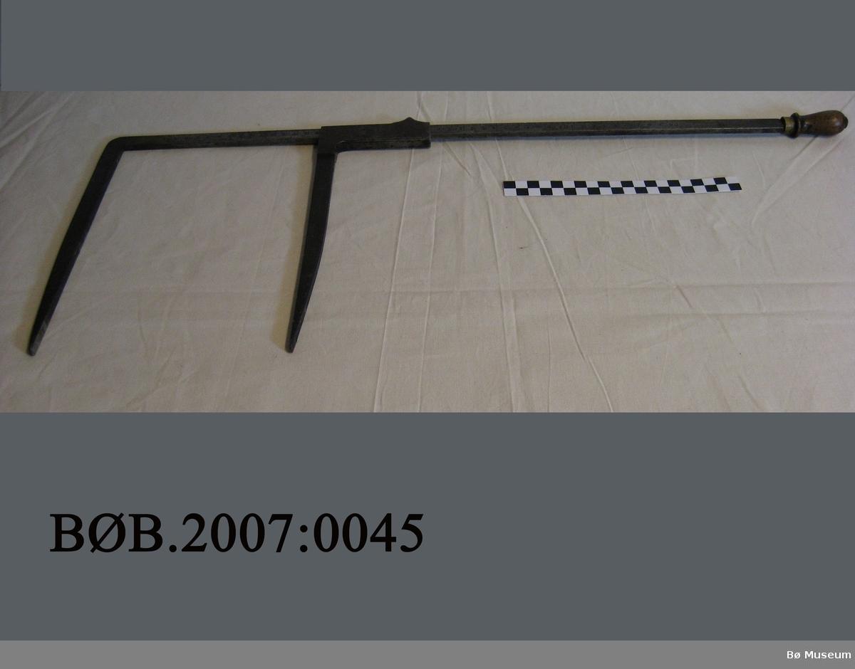 Tømmerklave av jern, eit lite trehandtak og messingring. Mål 0 - 50 cm og 0 -18 tommar