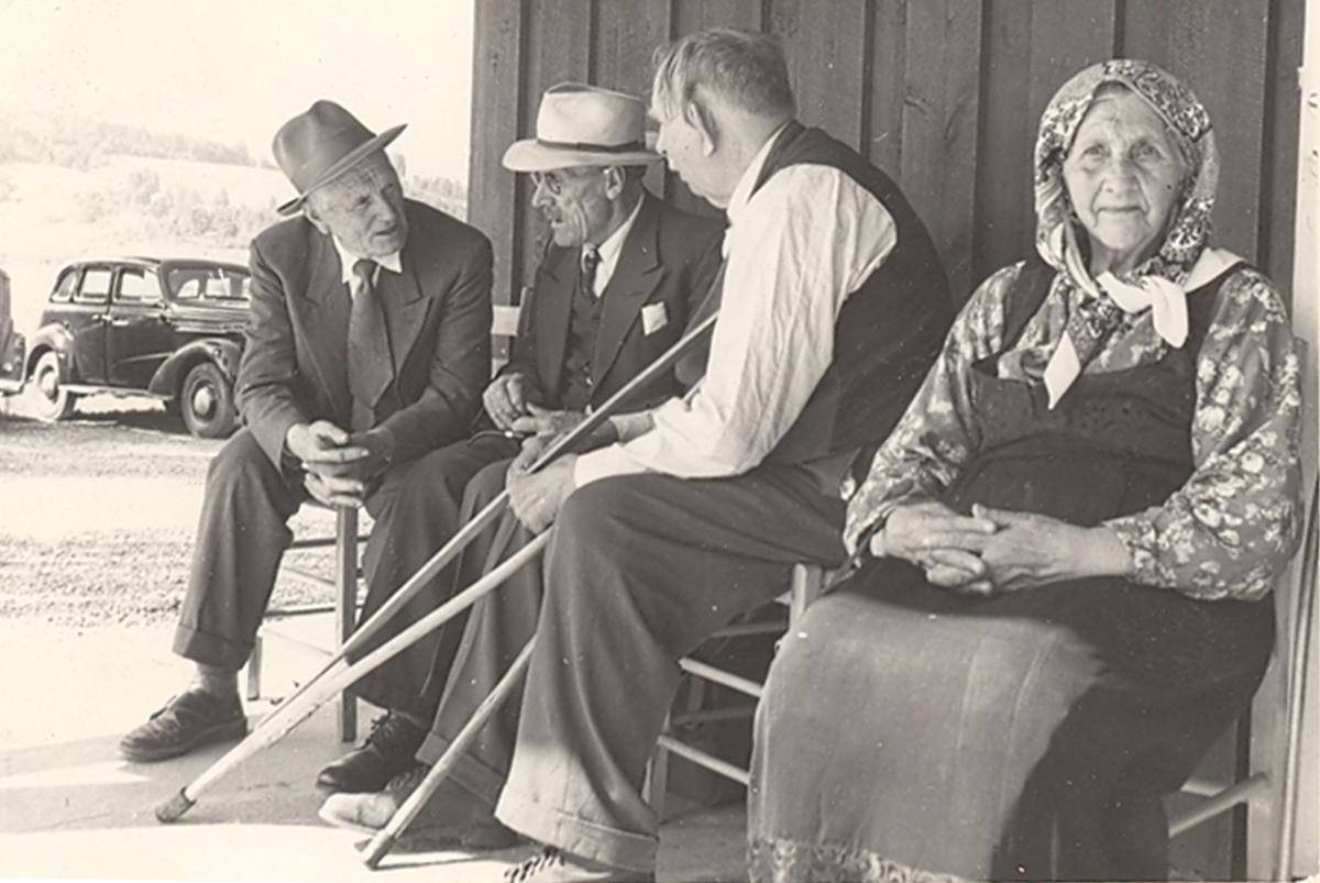 Fire personar sit på ein benk ved Sandvin der det er dyrskue. Frå v. Halvor Skogen Skrikerud, Torstein A. Haugerud, Tor Sisjord. Kvinna er ukjent.