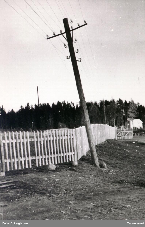 Telefonstolpe med slagside ved et gjerde, i nærheten av Åsbygda sentral Romedal i Stange.