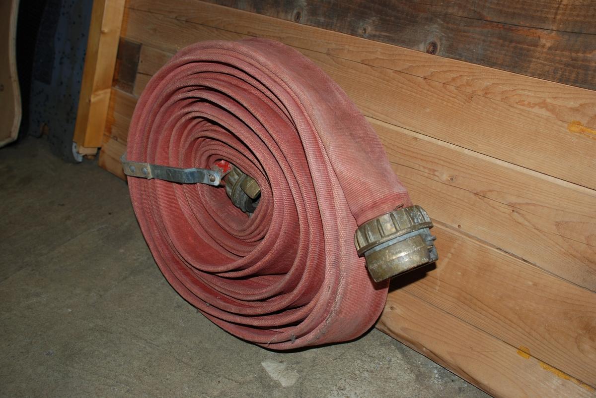 Brannslange i tekstil, rullet sammen. slangen har kupling i hver ende. Lærreim er festet rundt rullen for oppheng