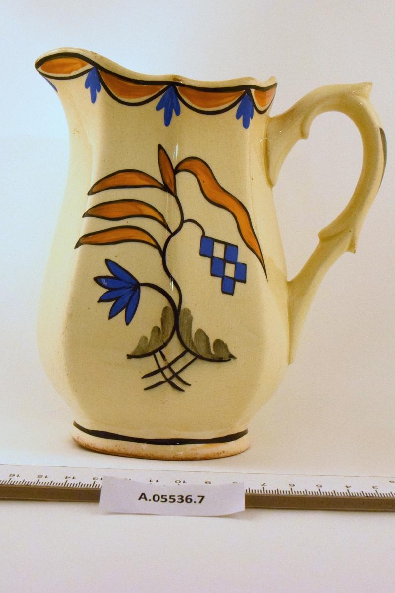 Mugge til servise i off-white glasur. Dekor RAKLER: kantet  i gultt/blått/sort mønster. Midtstilt dekor i tilsvarende farger og grått.
