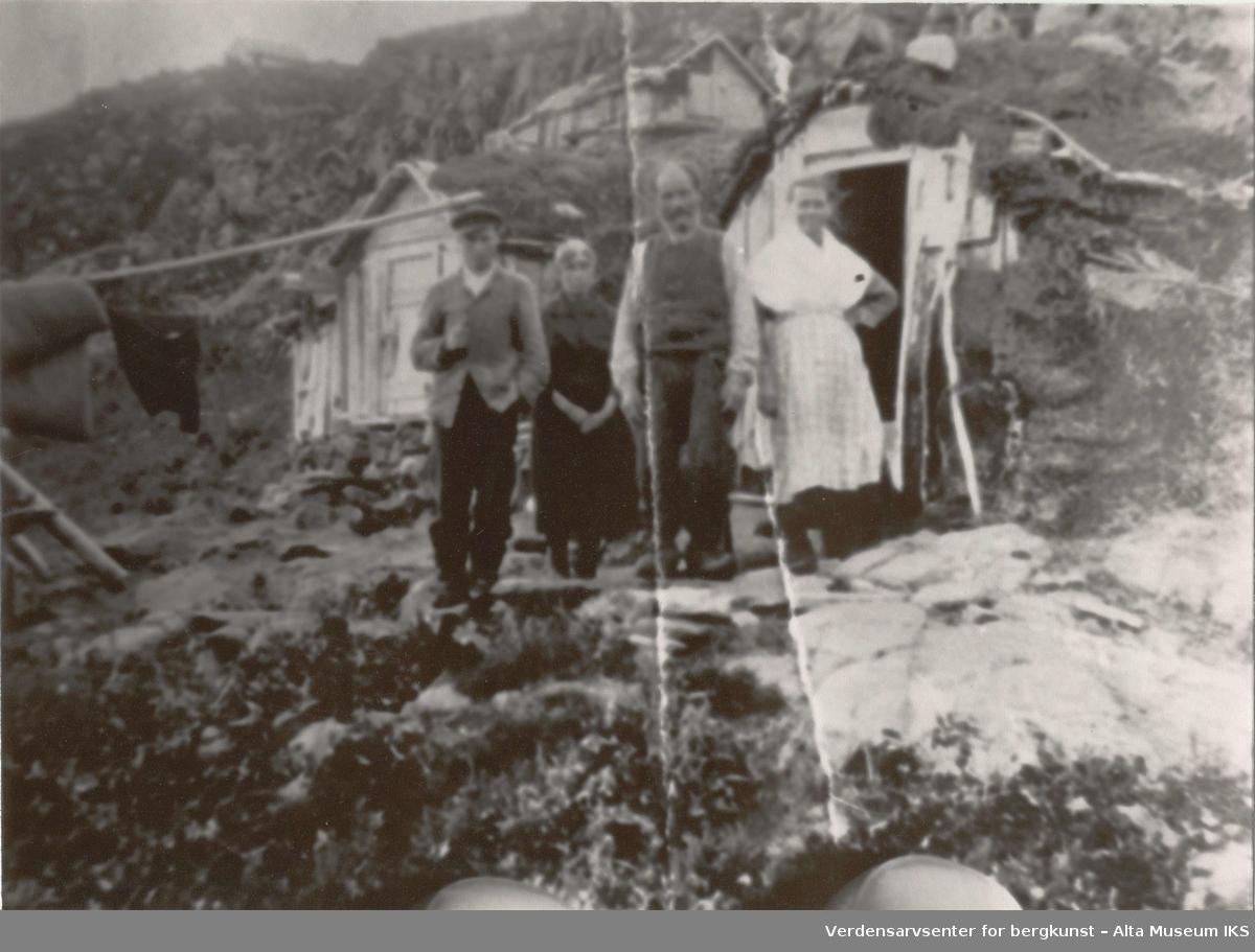 Hus/gamme i fjellsida, delvis dekt av torv. Kvinne, mann, ung kvinne, ung mann.