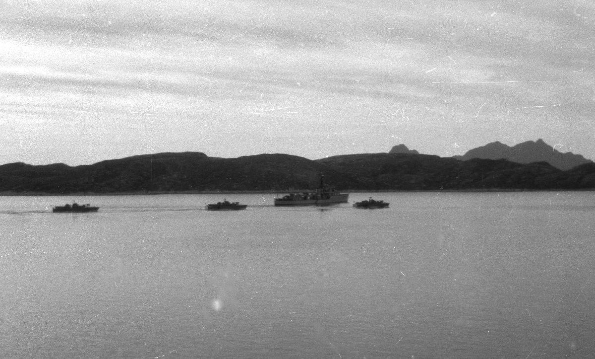 Landskap. Flere militære farkoster på vei inn mot Bodø havn. I bakgrunn Hjertøyene og Landegode.