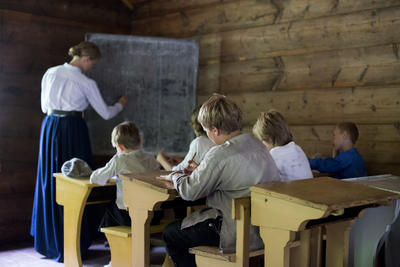 Children at their desks in the old school house while teacher writes at the black board