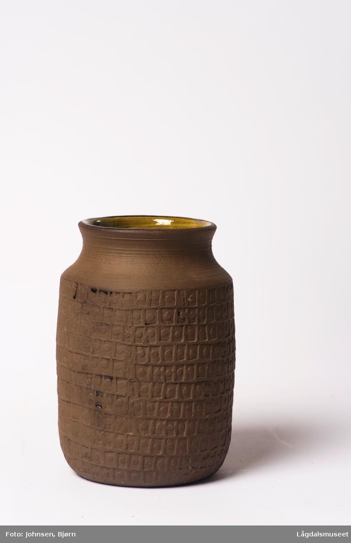 Vasen er uglasert og fylt med ornamenter i relieff.