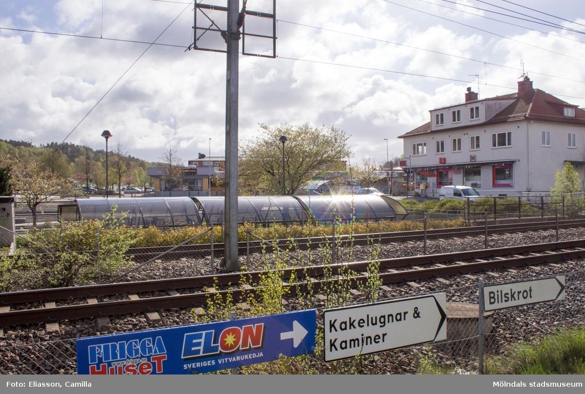 Vy över järnvägsspår och servicebutik (vit byggnad) från Bangårdsvägen i Kållereds centrum. I bakgrunden syns Vommedalsområdet, gul byggnad med Nisses pizza samt restaurang och parkering.