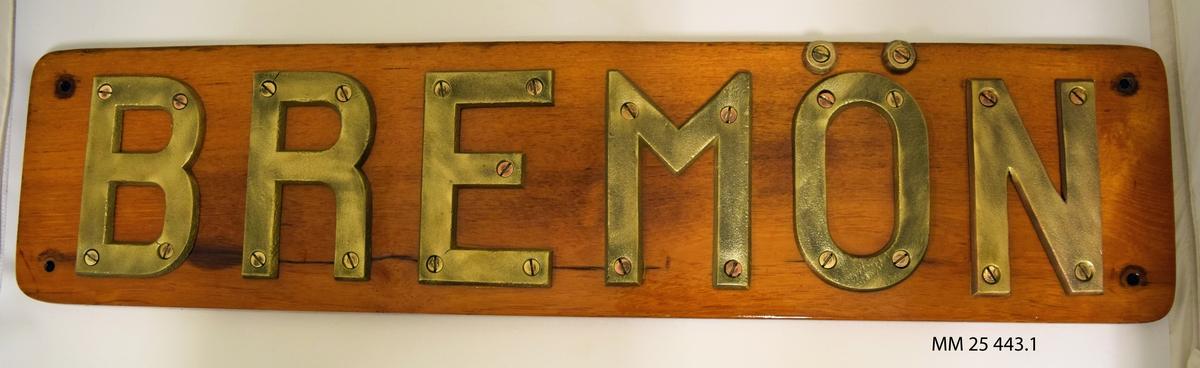 """Namnbräda. En rektangulär träplatta, fernissad, med bokstäver i stål skruvade i plattan bildar namnet """"BREMÖN""""."""