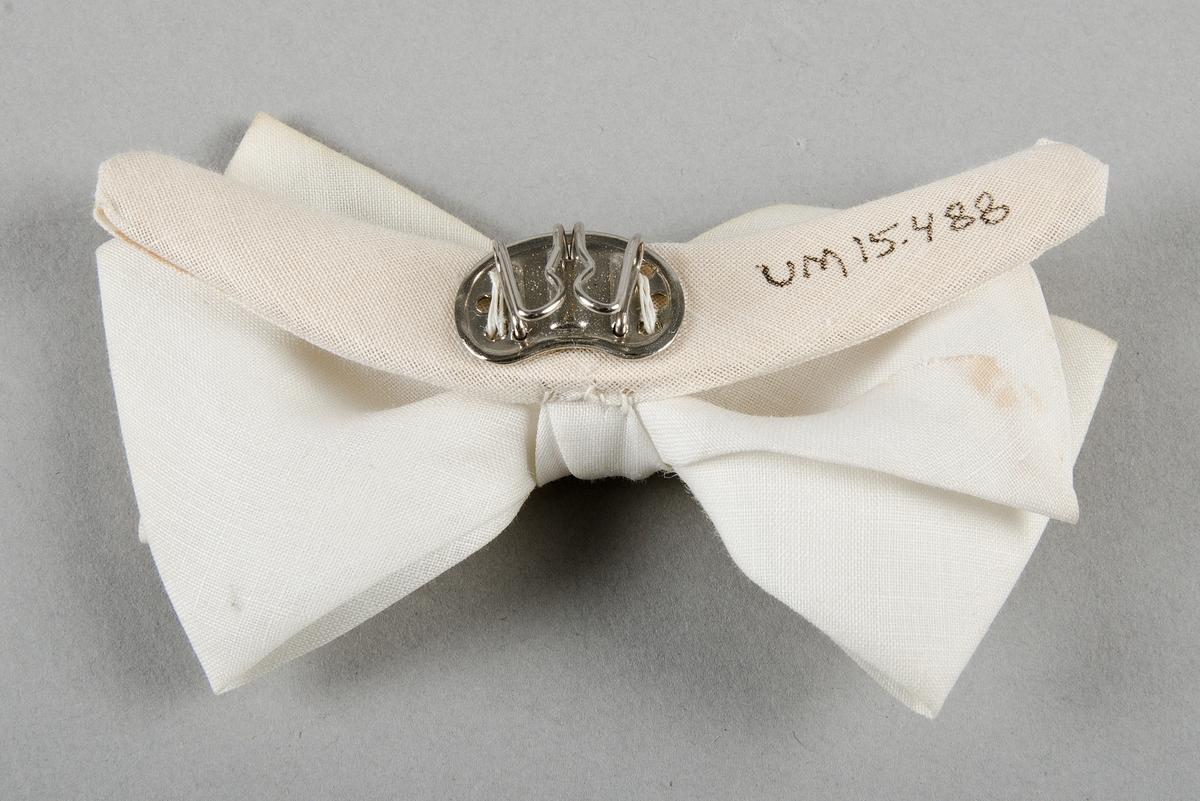 Fluga av vitt tuskaftat tyg. Fästes med metallhållare.  Förvaras i ask UM15481 tillsammans med lösmanschetter UM15482 - UM15484 och flugor UM15485 - UM15489.