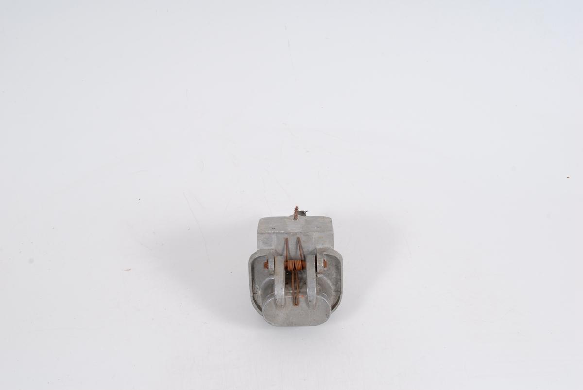 Form: Fjærbelastet lokk over stypslet. Trepols. Bakplaten har hull til skrue feste