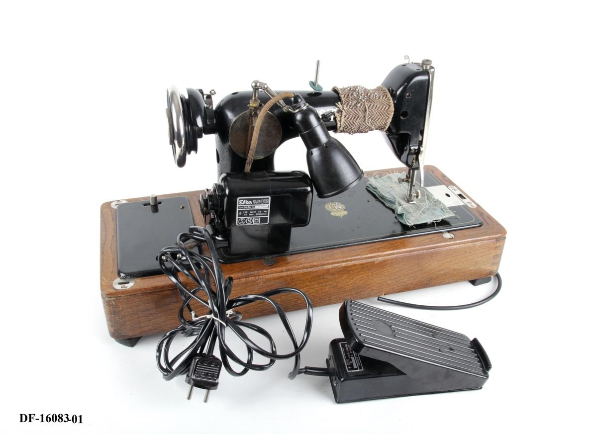 Symaskin på tresokkel, med tilhørende lokk med lås og håndtak. Symaskinen er utstyrt med lampe og  elektrisk motor, festet på baksiden med ledning og pedal.