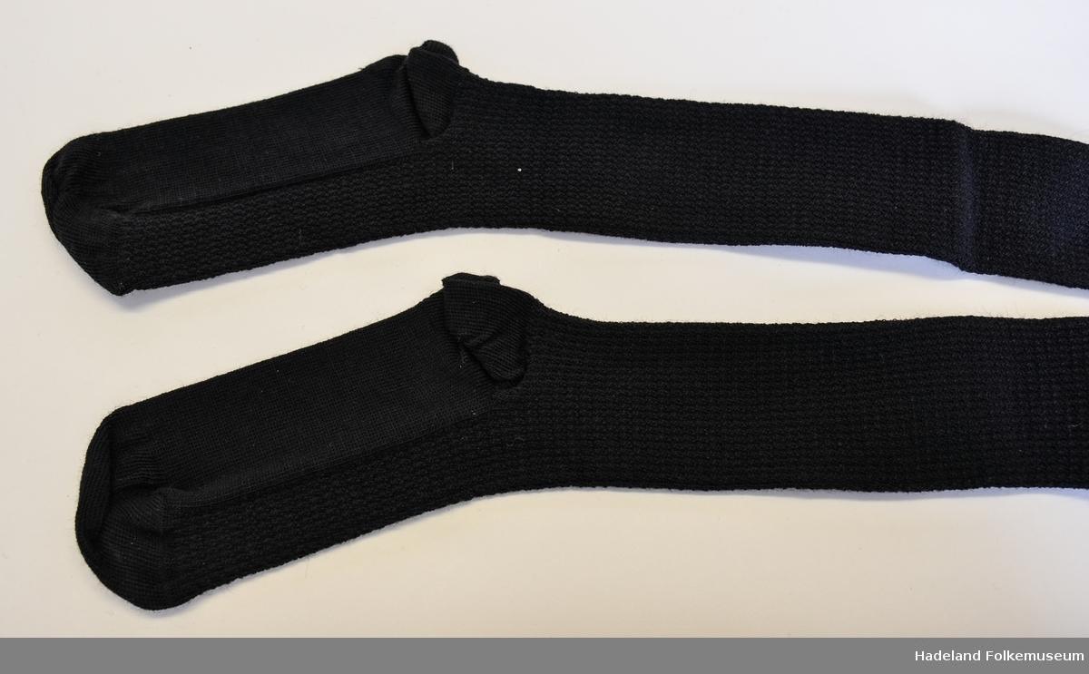 Strømper, 1 par, kvinne. Svart, ull og nylon. 14cm vrangbord. Mønstret legg og vrist. Prislapp mrk 14,95,- 10(str) Trykt på foten: Ull og crepenylon i hvitt og rødt.