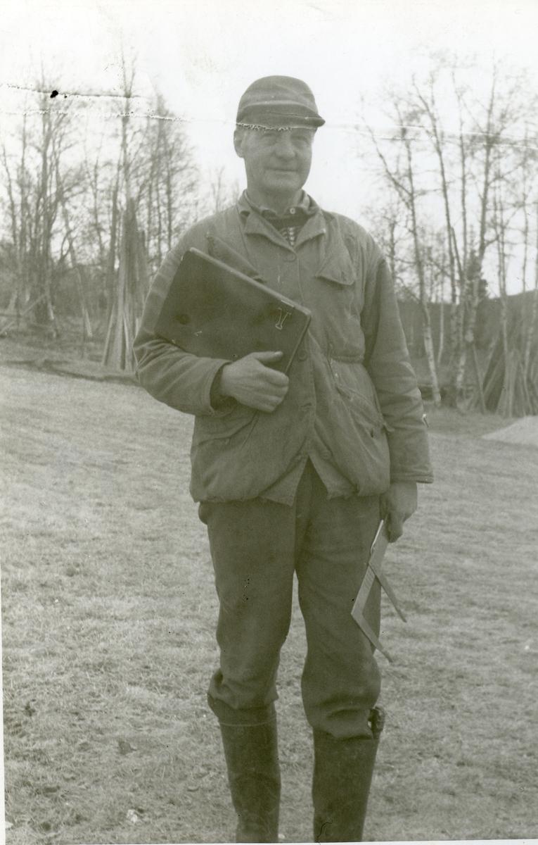 Mann med notatbok og måleutstyr foran noen trær. Mannen er iført gummistøvler og lue.