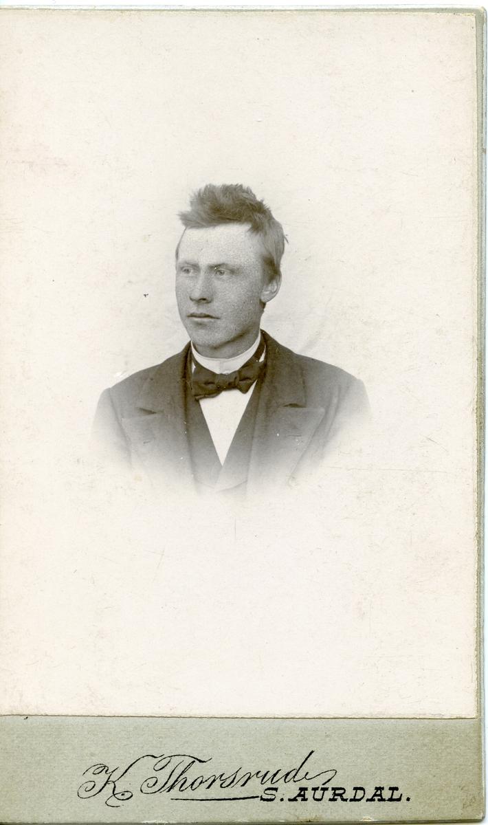 Halvportrett av mann iført dress med skjorte og sløyfe.