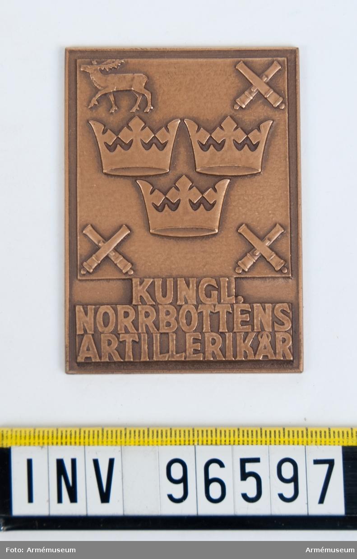 Plakett i brons för Norrbottens artillerikår. Stans 13824, härdad 1942-04-19. Reducering, puns och stans till plakett, 52x72 mm. Tre kronor jämte korslagda kanoner och ren, jämte inskription KUNGL: NORRBOTTENS ARTILLERIKÅR. Modell av Eugen Erhardt.