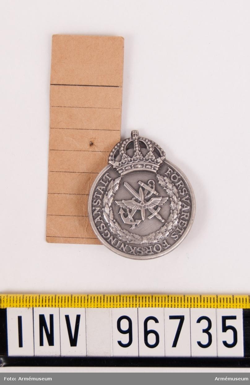 Mössmärke i silver för Försvarets forskningsanstalt. Mössmärke upptagande ankare, svärd och bevingad propeller, krönt av kungl. krona, omgivet av krans. Stans nr 23214. Stans härdad 1956-01-17.