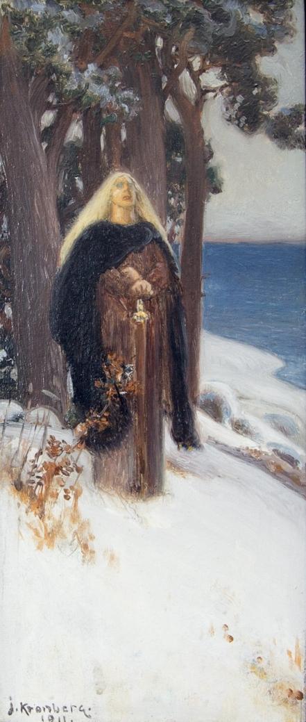 Ung kvinna, helfigur, med lång rödbrun klänning och lång svart kappa stående i dagsljus i ett snötäckt landskap med tallar och sjö.