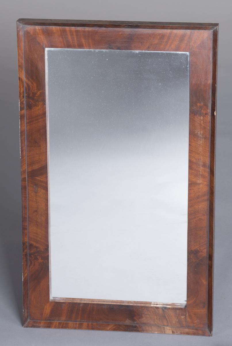 Rektangulært speil med treramme. Rammen har trolig mahogny-finér og er lakkert. Stram, enkel utforming.