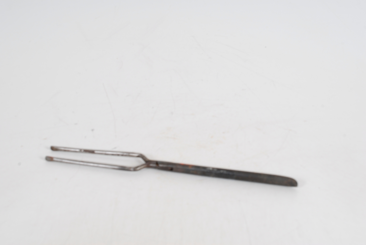 Form: lang tang der en rund pinne går inni en bøyd, tynne pinner i håndtaket