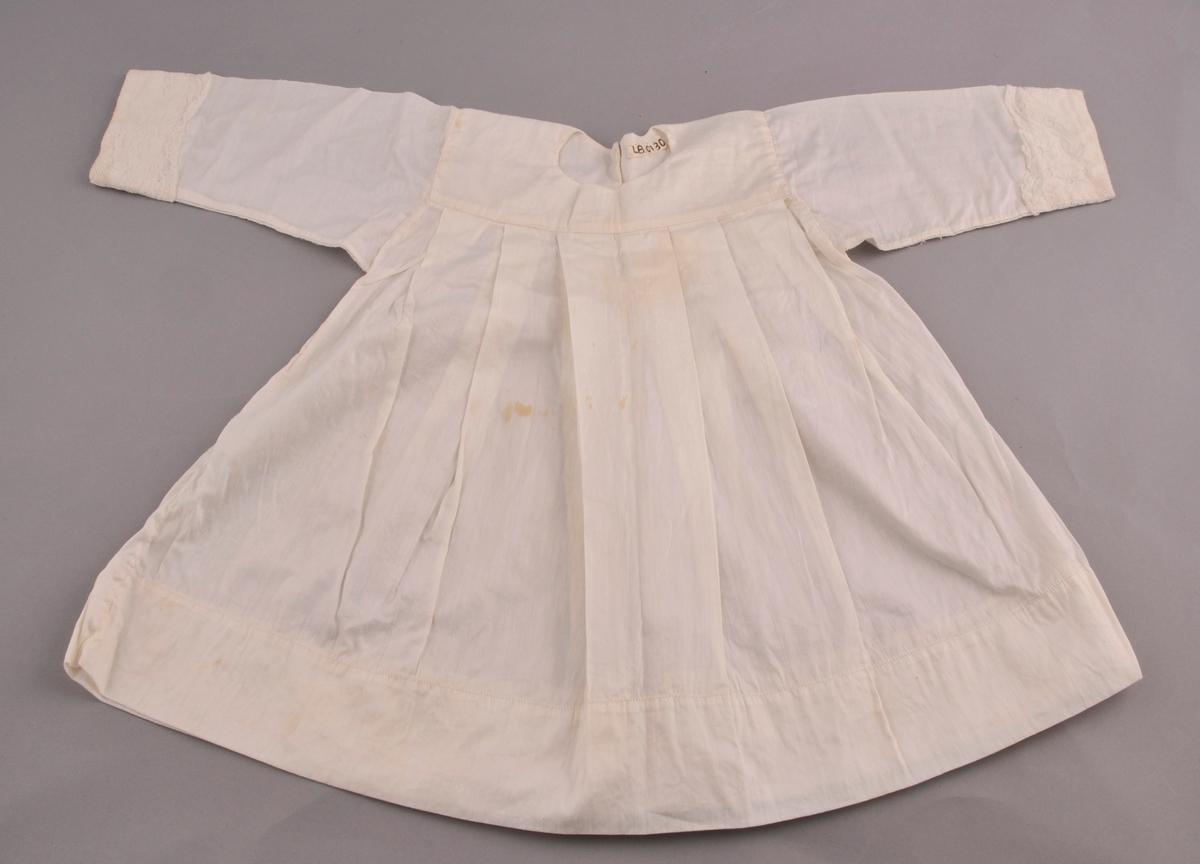 Kvit barnekjole i blankt, silkeliknande tøy. (Truleg blanding av bomull og silke). Sydd på maskin og for hand. Bersetykke i dobbelt stoff, med rund halsopning og splitt i ryggen. Splitten har to trykkknappar. Skjørtet på kjolen er lagt i faldar og sydd fast til berestykket. Nokså brei fald nederst, sydd med maskin.