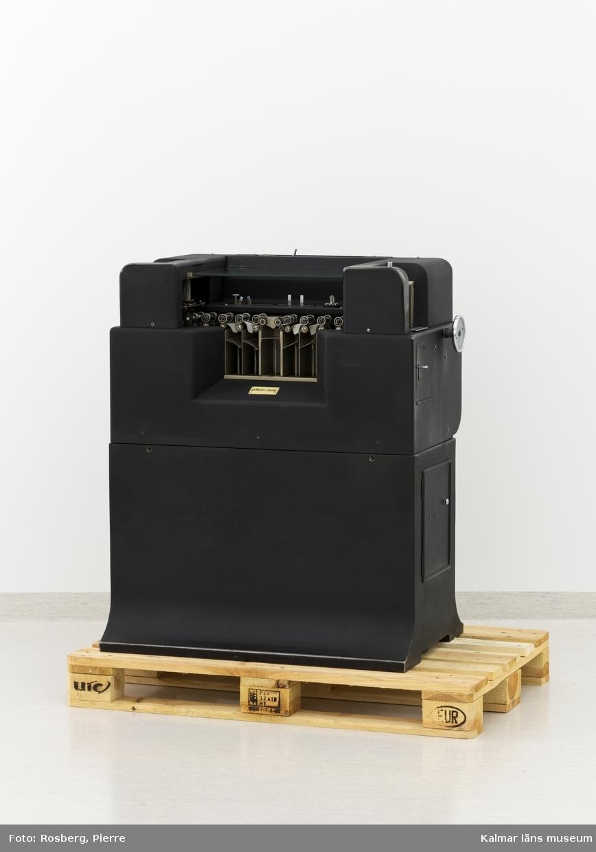 KLM 28585:7. Hålkortsmaskin, kollator. Användes för att plocka ihop två sorterade hålkortsbuntar till en sorterad kortbunt eller för att matcha kortbuntarna i enlighet med gjorda inställningar. Av svartlackerad metall. På båda kortsidor matas hålkorten in för att sedan sorteras automatiskt enligt de valda inställningarna. Korten hamnar i de olika avläggningsfacken, sammanlagt fem stycken. På maskinen diverse luckor som går att öppna. Inuti maskinen sitter en motor samt diverse elektronik. Upptill en glasskiva och under den diverse knappar och reglage. På maskinen några fastskruvade metallskyltar, samtliga med information om tillverkaren och produktionen, bl.a: POWERS SAMAS ACCOUNTING MACHINES ENGLAND MACHINE NO 332/1427. Till maskinen hör en skyddshuv av mörkgrön galon med text: POWERS FOUR INTERPOLATOR.