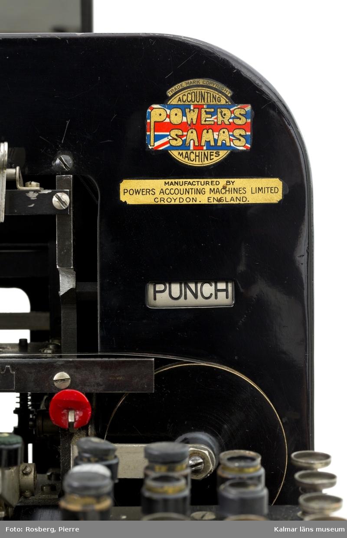 KLM 28585:2. Hålkortsmaskin, stansmaskin. Användes för stansning av hål i hålkorten. Stansmaskin av svartlackerad metall på fyra ben. Till höger ett tangentbord, i mitten utrymme för hålkort samt stansar. Undertill en plasthuv för uppsamling av de utstansade pappersbitarna. Maskinen var troligen från början helt mekanisk men har senare elektrifierats och försetts med en motor som sitter på baksidan. Baktill en vinklad spegel som användes för att kontrollera att korten kom ut på baksidan av maskinen efter stansningen. Till vänster en knapp för påslagning och baktill en svart elsladd. På maskinen diverse fastskruvade metallskyltar samt ett klistermärke, samtliga med information om tillverkaren och produktionen, bl.a: POWERS SAMAS ACCOUNTING MACHINES ENGLAND. På baksidan en mindre mässingsskylt med instansat nummer: 0378. Till maskinen hör en skyddshuv i mörkgrön galon, troligen ej ursprunglig.  Till maskinen hör en liten huv av svartlackerad metall som suttit på undersidan med samma funktion som plasthuven. I plasthuven låg diverse runda pappersbitar, dessa har samlats i en påse och förvaras med maskinen.