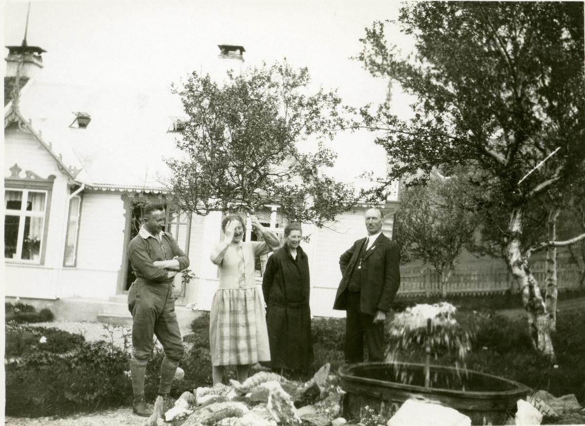 To kvinner og to menn avbildet ved en liten fontene, i en hage foran et bolighus. Mannen til høyre er Olaus Islandsmoen.