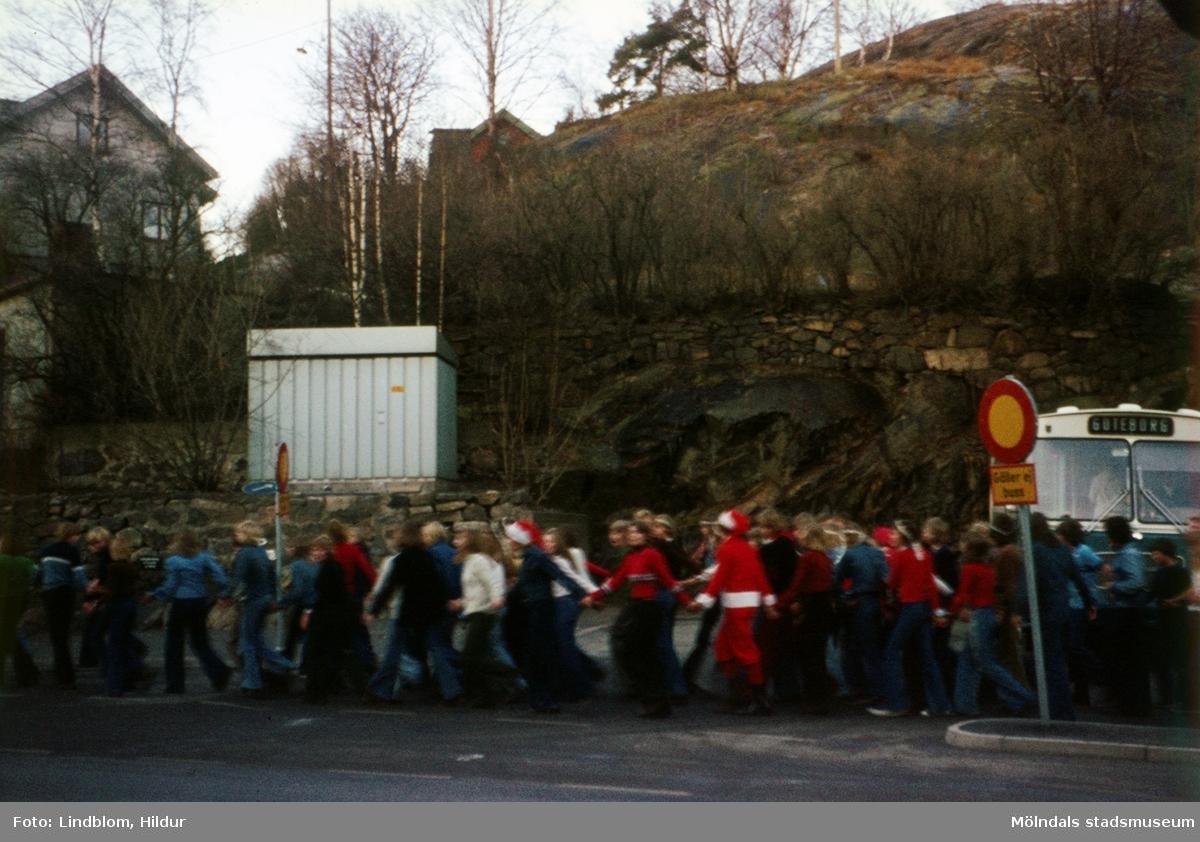 En samling ungdomar tågar förbi en busshållplats vid Gamla Torget i Mölndal, 1970-tal. Några av ungdomarna verkar ha glitter i håret och någon bär en tomtedräkt.  För mer information om bilden se under tilläggsinformation.