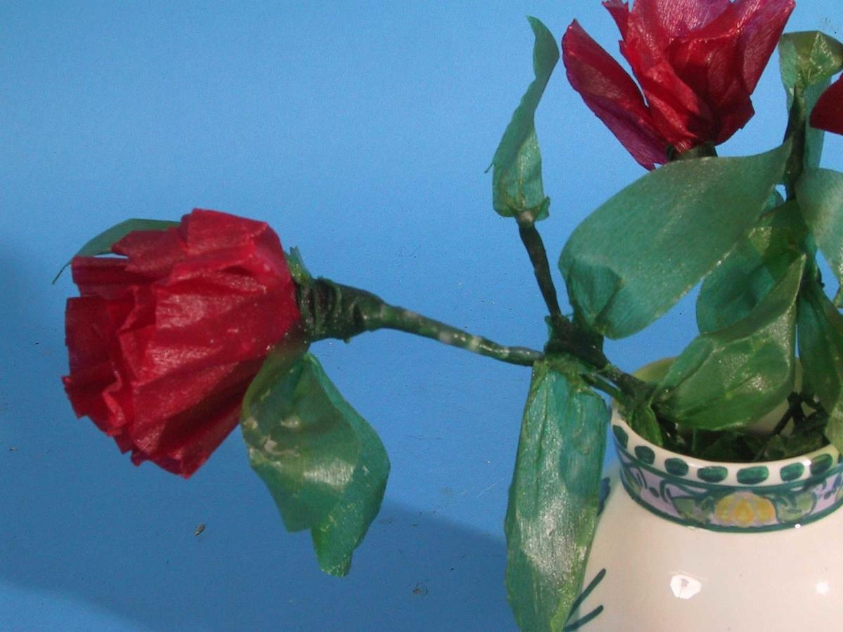 En bukett kunstige blomster, laget av ståltråd, krepp papir, voks i forskjelige farger.  Hver blomst L. fra 21 til 50 cm.  Ståltråd i stilk og bladstilk, omvunnet med grønt krepp-papir, med grønne blad, blomst av krepp-papir, blomster  og blad vokset. 7 røde, 4 fiolette, 3 gule.