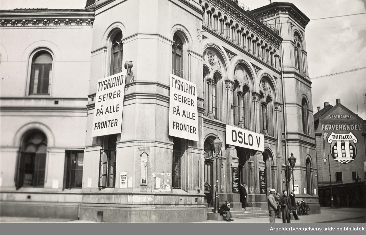 """Ole M. Engelsens fotografier fra okkupasjonsårene i Oslo..Oslo Vestbanestasjon. Oslo V. """"Tyskland seirer på alle fronter""""..Foto 22 juli 1941."""