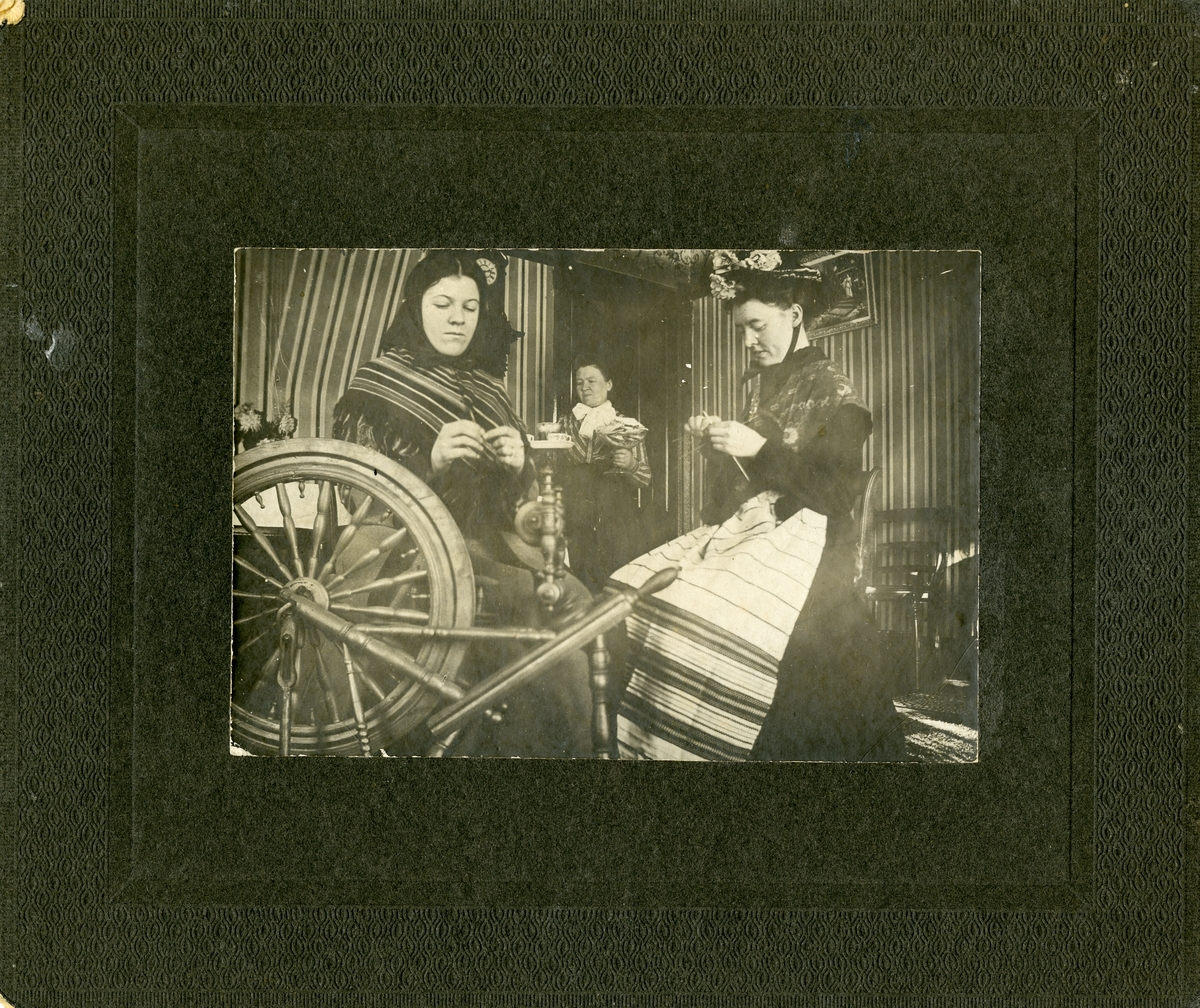 Ella og Emma Knatvold sitter foran en rokk og strikker. Bak står mora Tonette.