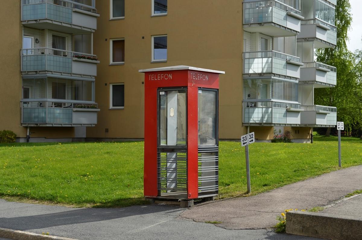 Denne telefonkiosken står i Refstadsvingen 1 ved Bjerke travbane, og er en av de 100 verna telefonkioskene rundt om i Norge. De røde telefonkioskene ble laget av hovedverkstedet til Telenor (Telegrafverket, Televerket) Målene er så å si uforandret.  Vi har dessverre ikke hatt kapasitet til å gjøre grundige mål av hver enkelt kiosk som er vernet.  Blant annet er vekten og høyden på døra endret fra tegningene til hovedverkstedet fra 1933. Målene fra 1933 var: Høyde 2500 mm + sokkel på ca 70 mm Grunnflate 1000x1000 mm. Vekt 850 kg. Mange av oss har minner knyttet til den lille røde bygningen. Historien om telefonkiosken er på mange måter historien om oss.  Derfor ble 100 av de røde telefonkioskene rundt om i landet vernet i 1997. Dette er en av dem.