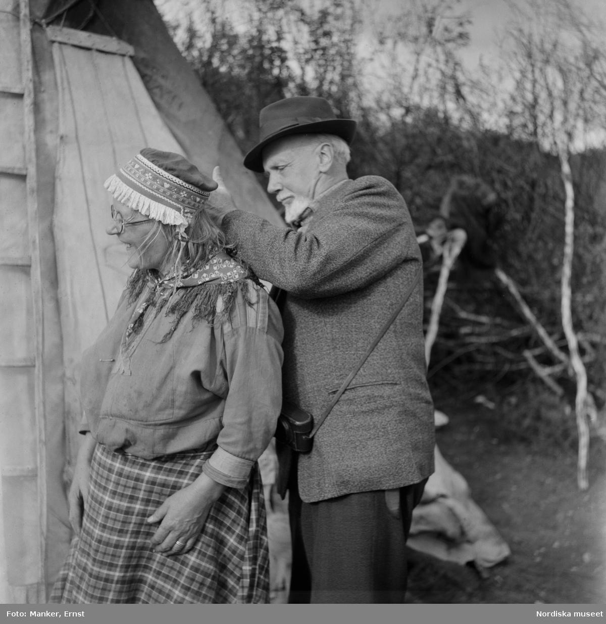 """Motiv från Kummaätno. """"Doktor Hallström söker kurera Anders Pongas hustru Margit för ont i ryggen."""" Man med vitt skägg undersöker kvinna, i bakgrunden en kåta."""