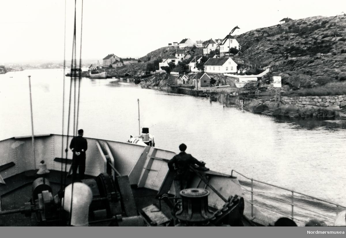 Kystbebyggelse i Norge tatt fra skip med baugen i forgrunnen.