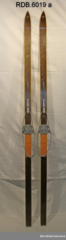 Et par brune, laminerte treski med trekvite kanter. Rund Rustad-logo på skituppen, stålkanter bak og lignostonekanter under. Kvit påskrift. Påmontert Gresvig  kandaharbindinger og orange fotplate i plast. Denne er stiftet fast til skiet.