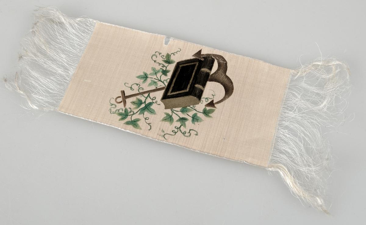 Bokmärke av beigefärgat sidenband  på vilket är målat ett ankare, en bok och en murgrönekvist i brunt, svart, grönt och guld. Upprepad frans på kortsidorna.