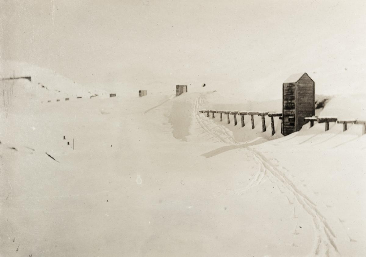Nedsnødd snøoverbygg ved Thorbjørnstøl, like øst for Finse stasjon. Avtrekkshatt for røyk fra damplokomotivene i forgrunnen.