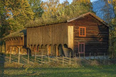 Brunlig toetasjers tømmerbygning med to rutete vinduer over hverandre i gavleveggen og tettet svalgang i andre etasje.