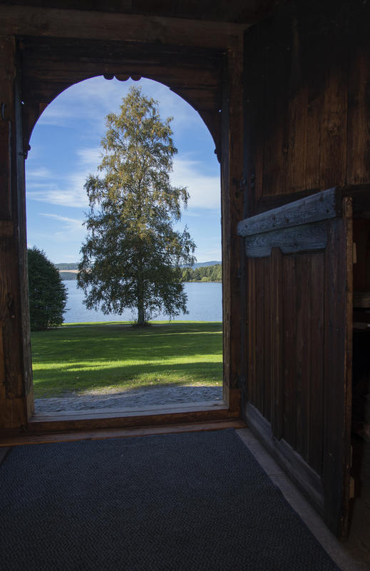 Nydelig utsikt over Rosenlundvika fra steinhellen utenfor den buede, todelte døra.
