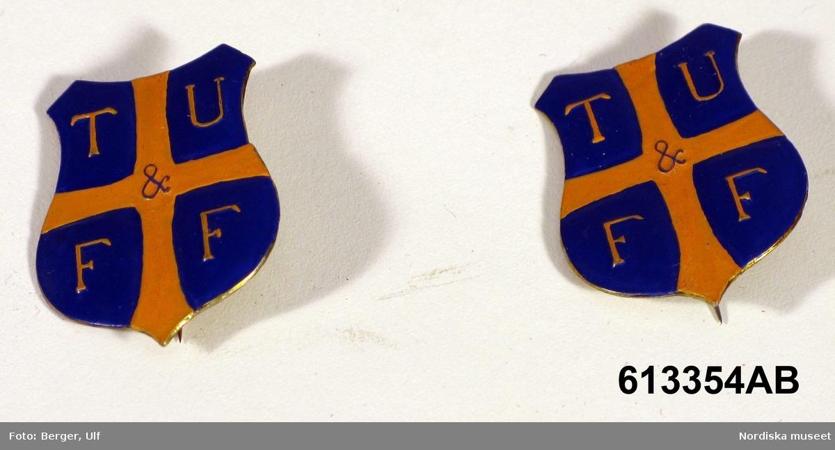 """Huvudliggaren: """"a-b, Föreningsmärke, föreningsnål, 2 st, metall, emaljerade. Blå sköld med gult kors. I fälten bokstäverna T U F F. Tyresö Ulands- och fredsförening."""""""