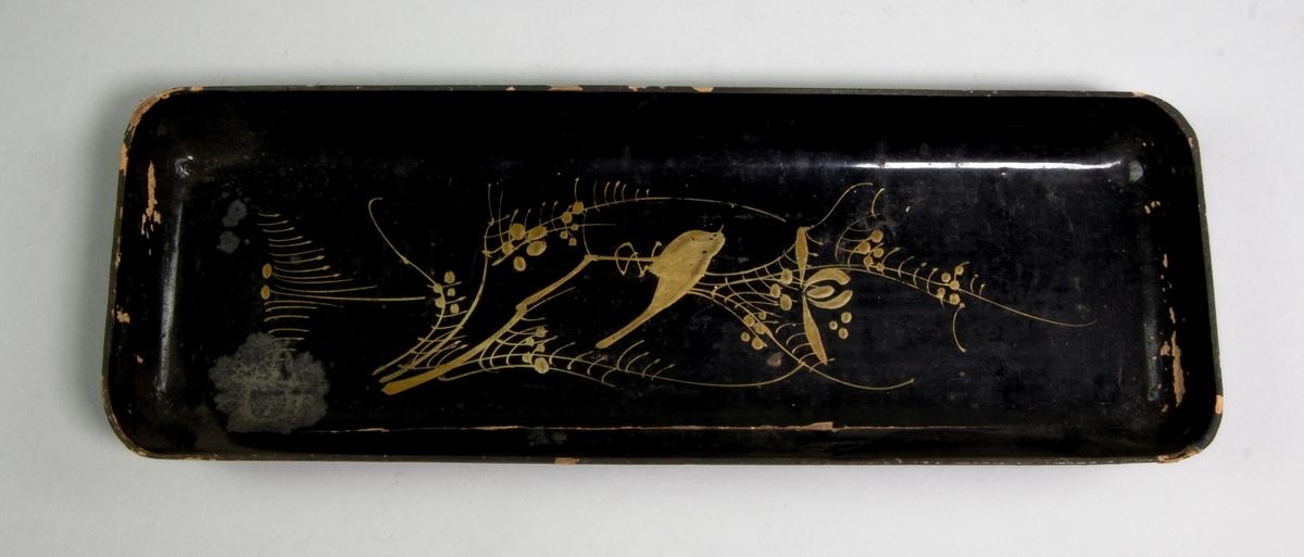 Pennfat av trä, rektangulärt med uppvikt kant. Svartlackerat med målad guldfärgad dekor i form av en fågel sittande på en blomkvist.