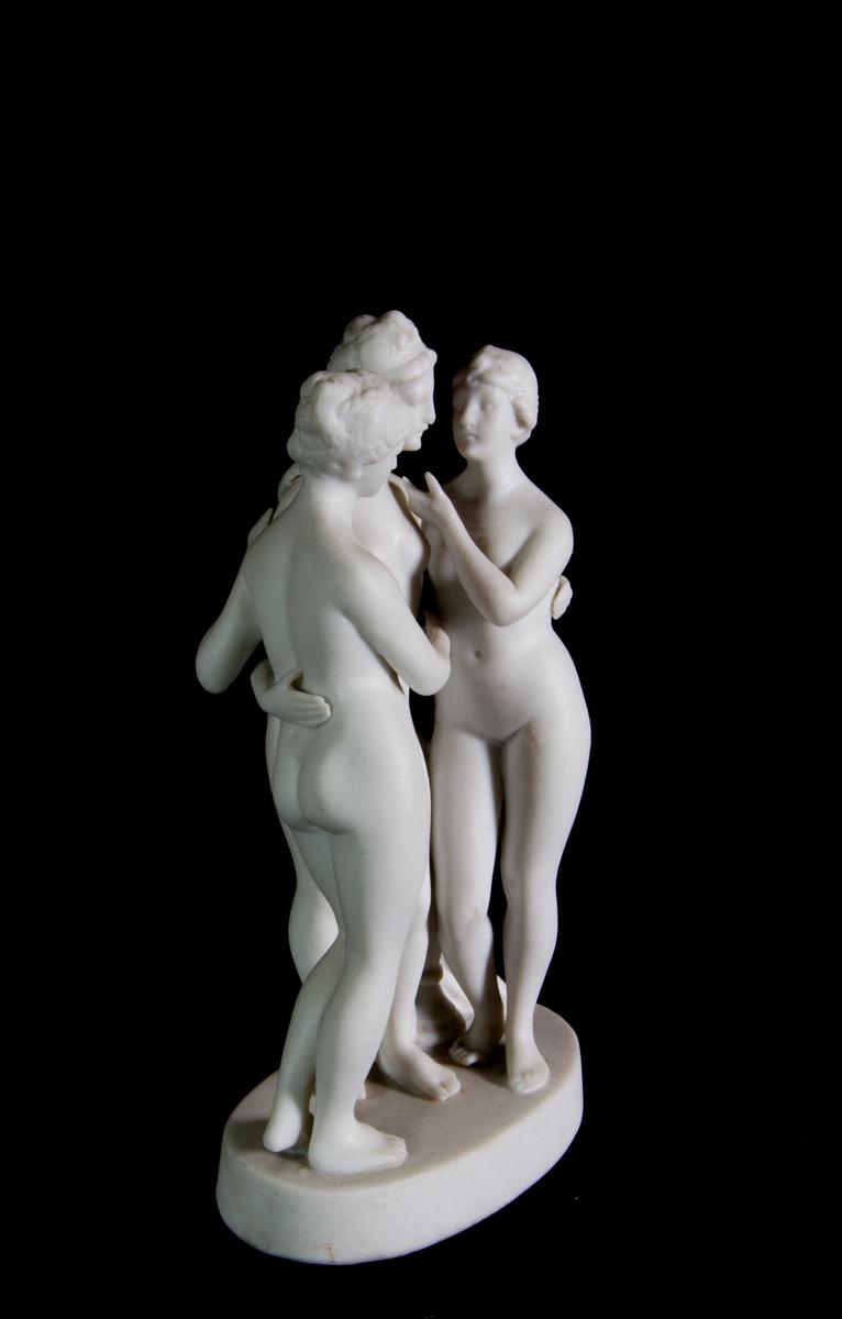 Studiemodell föreställande de tre gracerna i parian. De tre nakna kvinnorna i helfigur håller armarna om varandra. Bakom dem en draperad stubbe. Oval fotplatta.
