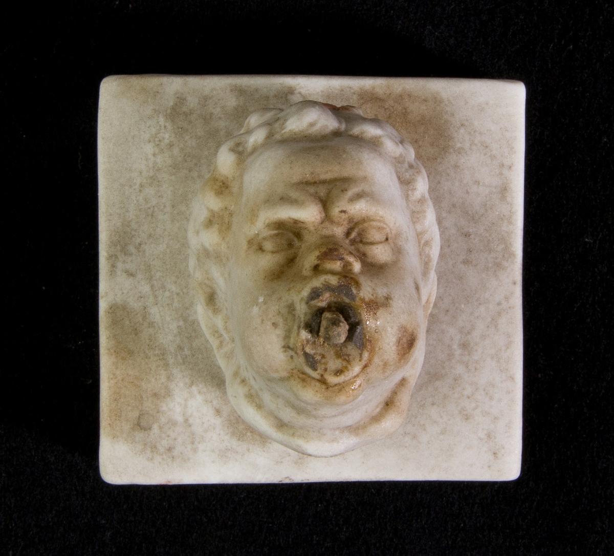 Studiemodell föreställande en mycket liten vattenutkastare i form av ett manshuvud med uppblåsta kinder. Järnten i munnen. Monterad på kvadratisk platta.