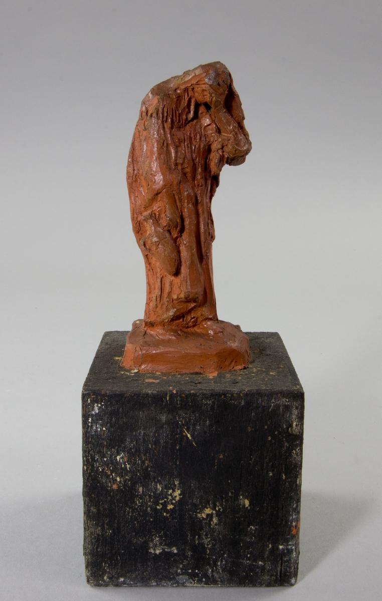 Kvinna i helfigur, stående med nedböjt huvud.