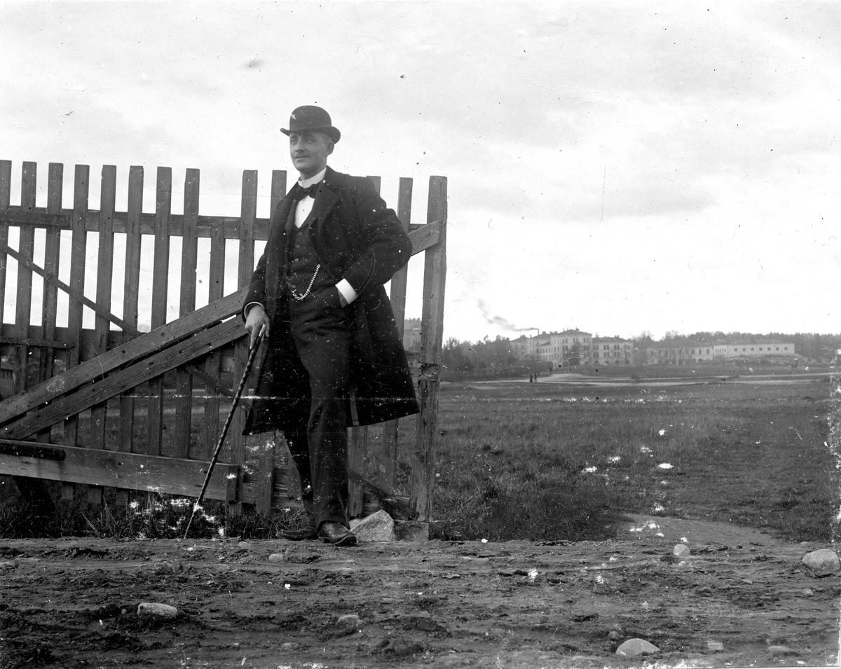 En man med käpp står vid ett staket år 1898. Fotograf Alfred Bergendahl. Givare H Bergendahl.