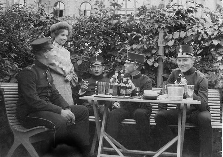 Några män i uniform har har slagit sig ner i en liten berså med ett antal glas och flaskor, troligen med punsch. En av männen röker cigarr. Till vänster står en kvinna. Lundvik - Martin Lundvik (1883-    ), underlöjtnant vid Hälsinge regemente.Sparre - ev. Carl Erik Sixtensson Sparre (af Rossvik) (1881-1962) löjtnant vid Norrlands artilleriregemente, Östersund. Senare kapten.Nykvist - ev. Gustaf Alarik Nyqvist (1883-   ), löjtnant och 3:e adjutant vid Jönköpings regemente.Axel Åkerman (1882-    ), underlöjtnant vid Hälsinge regemente.Källor: Sveriges Rikskalender 1908, s. 174,176. Svensk Adelskalender 1904, 1936,1949, 1967. Svensk Släktkalender.