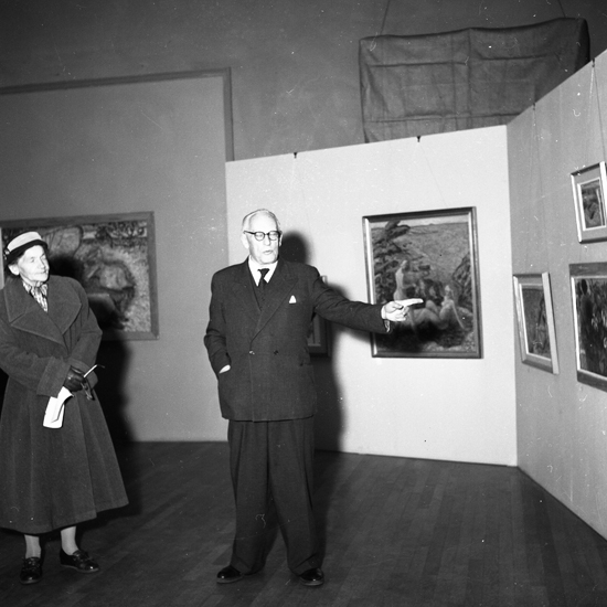 SM utställning Edward Hald. 1957.03. Foto av glaskonstnären Edward Hald som förklarar något för besökare.