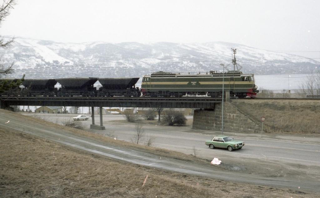 Malmvogner lastet med olivin skiftes fra Narvik Havn, Fagerneskaia og opp til Narvik stasjon og videre til Øvre Rang. Skiftet  trukket av et elektrisk lokomotiv av type El. 15, Skiftet passerer over brua over Sjøbakken i Narvik.
