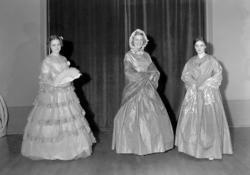 Ett grupporträtt med tre kvinnor i klänningar, paraply och s