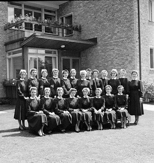 Bild på en sjuksköterskeklass i uniform med hättor.En tegelbyggnad syns i bakgrunden.